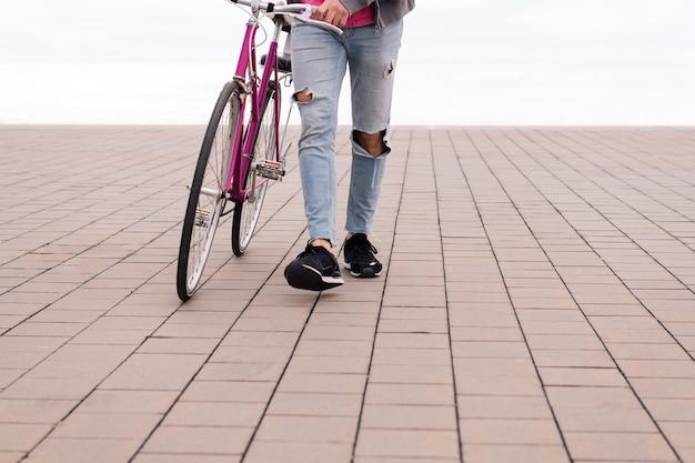 Jeune homme méconnaissable marchant en poussant un vélo