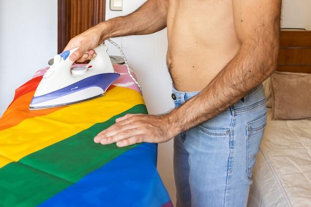 Jeune homme méconnaissable torse nu, drapeau lgbt à repasser sur une planche à repasser