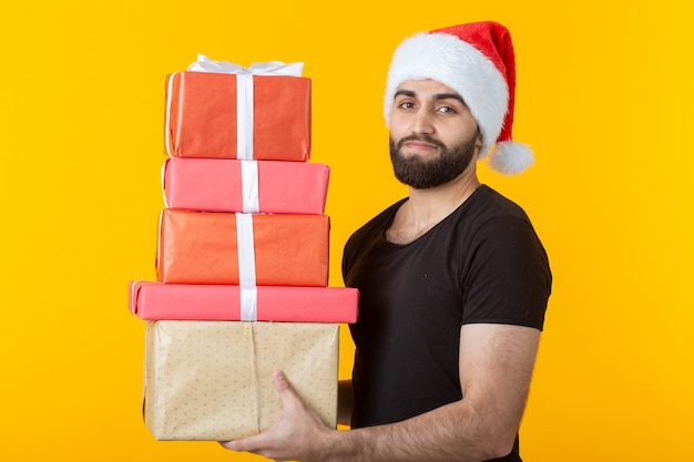 Jeune homme mécontent avec une barbe dans un chapeau de père noël détient cinq coffrets cadeaux posant sur un mur jaune. concept de cadeaux et salutations pour noël