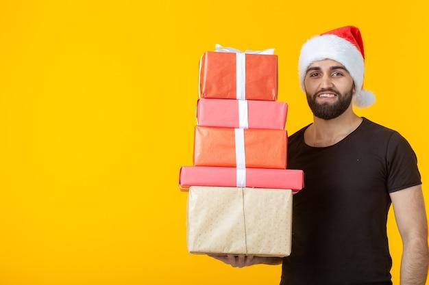 Jeune homme mécontent avec une barbe dans un chapeau de père noël détient cinq coffrets cadeaux posant sur un mur jaune avec copyspace. concept de cadeaux et salutations pour noël et nouvel an.