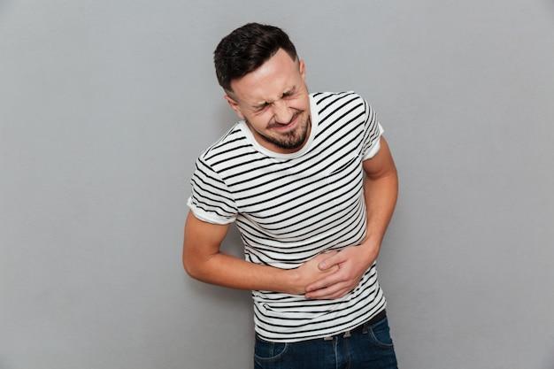 Jeune homme mécontent avec des sentiments douloureux tenant le ventre
