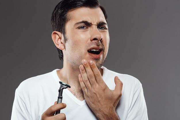Jeune homme mécontent de toucher le visage après s'être rasé sur un mur gris