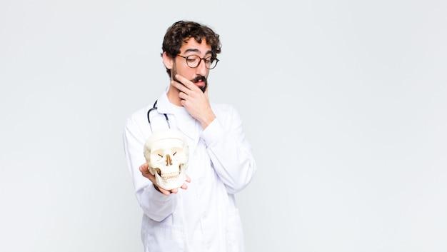 Jeune homme médecin barbu fou tenant un crâne humain