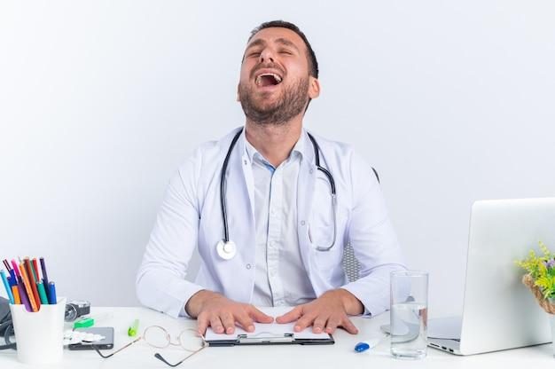 Jeune homme médecin en blouse blanche et avec un stéthoscope bouleversé pleurant fort d'être frustré assis à la table avec un ordinateur portable sur un mur blanc