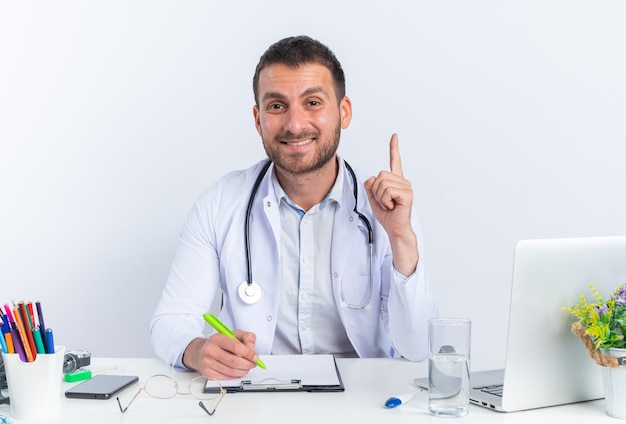 Jeune homme médecin en blouse blanche et avec stéthoscope souriant écrit confiant montrant l'index ayant une bonne idée assis à la table avec un ordinateur portable sur un mur blanc