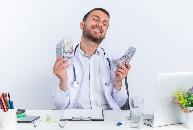 Jeune homme médecin en blouse blanche et avec stéthoscope tenant de l'argent heureux et excité assis à la table avec un ordinateur portable sur fond blanc
