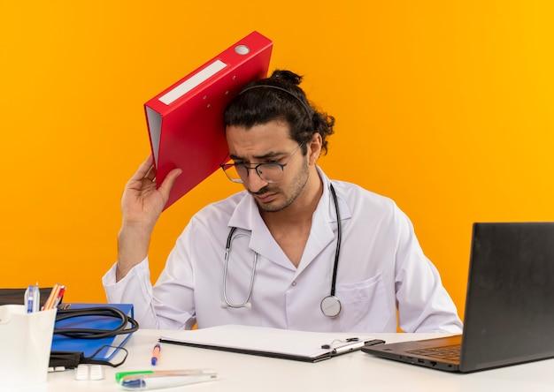 Jeune homme médecin confus avec des lunettes médicales portant une robe médicale avec stéthoscope assis au bureau
