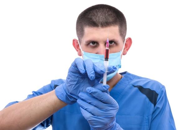 Jeune homme médecin examinant la seringue avec du sang du patient isolé