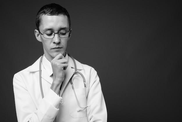 Jeune homme médecin avec des lunettes contre un mur gris en noir et blanc
