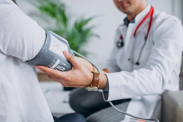 Jeune homme médecin avec patient mesurant la pression artérielle