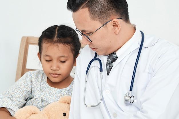 Jeune homme médecin pédiatre vérifiant fille