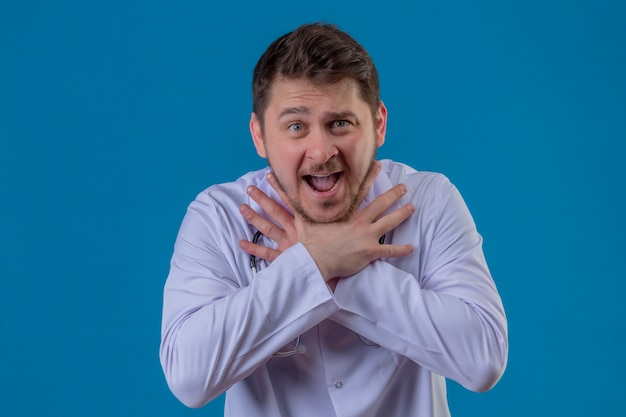 Jeune homme médecin portant blouse blanche et stéthoscope criant et essayant de s'étouffer sur fond bleu isolé
