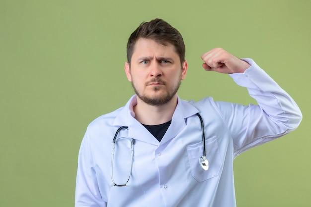 Jeune homme médecin portant blouse blanche et stéthoscope montrant les biceps avec un visage sérieux exprimant la force, concept gagnant