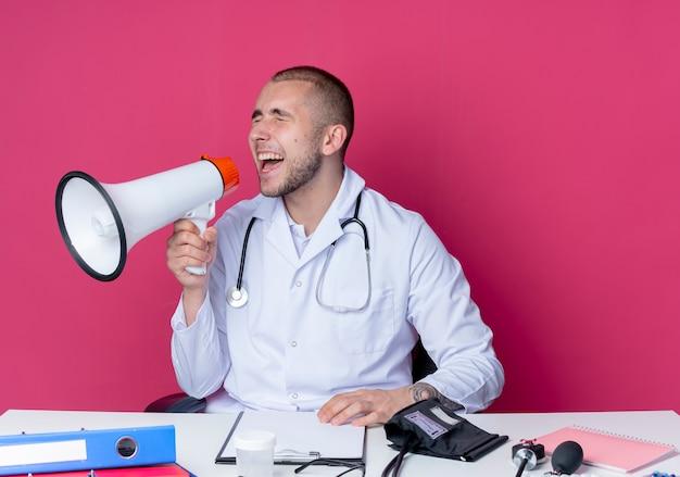Jeune homme médecin portant une robe médicale et un stéthoscope assis au bureau avec des outils de travail en tournant la tête à l'autre et en criant dans le haut-parleur avec les yeux fermés isolé sur fond rose