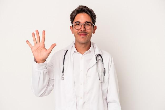 Jeune homme médecin de race mixte isolé sur fond blanc souriant joyeux montrant le numéro cinq avec les doigts.