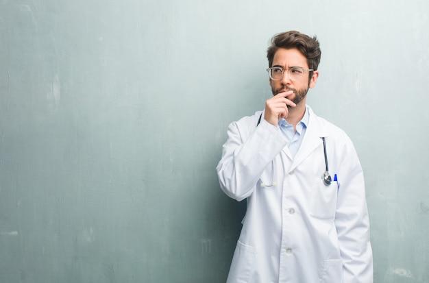 Jeune homme médecin sympathique contre un mur de grunge avec un espace de copie doutant et confus