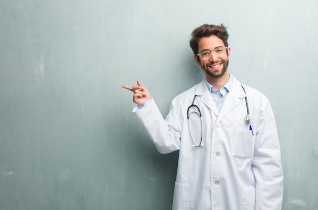 Jeune homme médecin sympathique contre un mur de grunge avec un espace de copie pointant vers le côté