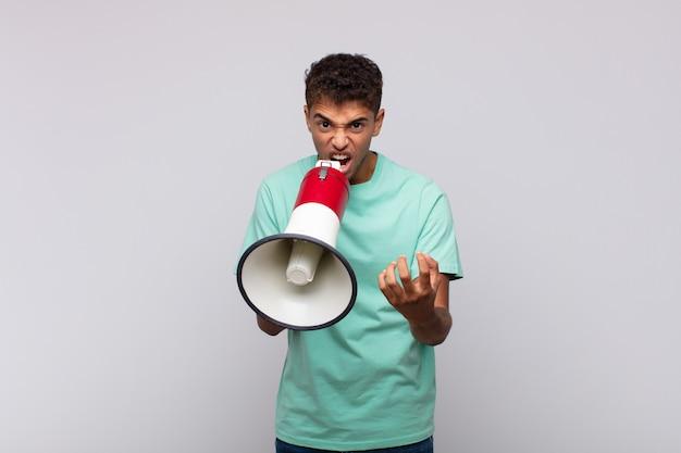 Jeune homme avec un mégaphone à la colère, agacé et frustré crier wtf ou quel est le problème avec vous