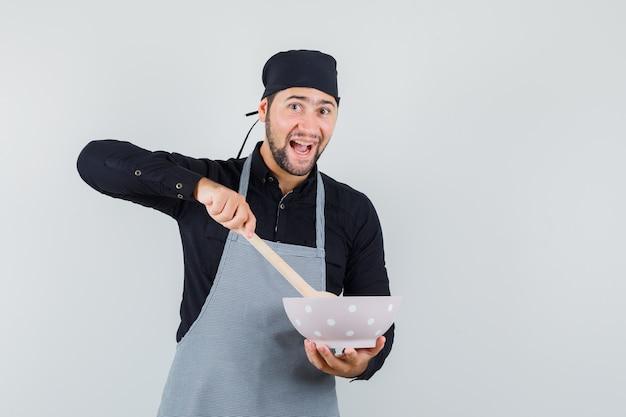 Jeune homme mélangeant le déjeuner avec une cuillère en bois en chemise, tablier et à la joyeuse. vue de face.