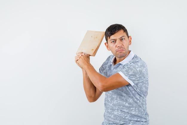 Jeune homme menaçant de planche à découper en t-shirt et à la colère