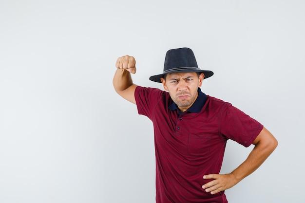 Jeune homme menaçant de poing en t-shirt, chapeau et semblant nerveux. vue de face.