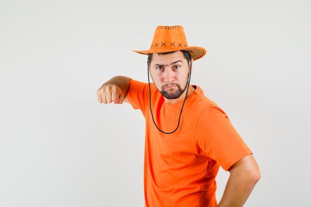 Jeune homme menaçant avec le poing en t-shirt orange, chapeau et regardant en colère, vue de face.