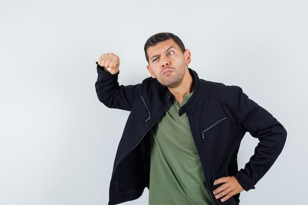 Jeune homme menaçant avec le poing en t-shirt, veste et l'air pensif, vue de face.