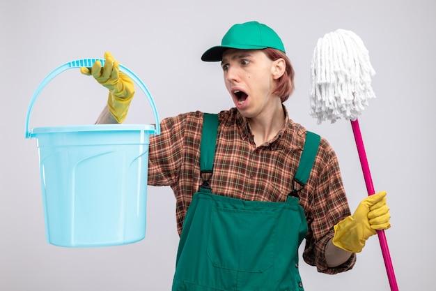 Jeune homme de ménage en combinaison chemise à carreaux et casquette portant des gants en caoutchouc tenant un seau et une vadrouille criant d'être confus et surpris