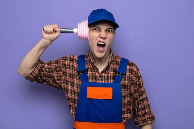 Jeune homme de ménage mécontent portant un uniforme et une casquette tenant le piston sur la tête
