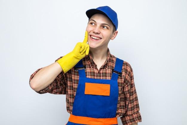 Jeune homme de ménage portant un uniforme et une casquette avec des gants isolés sur un mur blanc