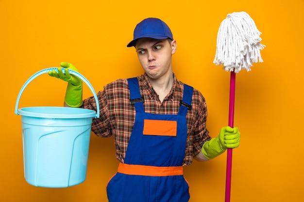 Jeune homme de ménage portant un uniforme et une casquette avec des gants tenant une vadrouille et un seau isolés sur un mur orange