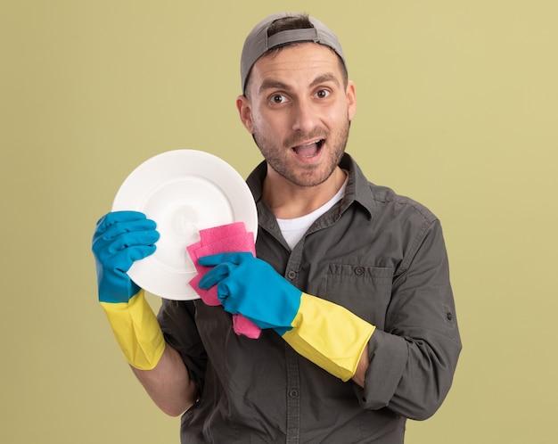 Jeune homme de ménage portant des vêtements décontractés et une casquette dans des gants en caoutchouc tenant une plaque et un chiffon à heureux et excité debout sur mur vert