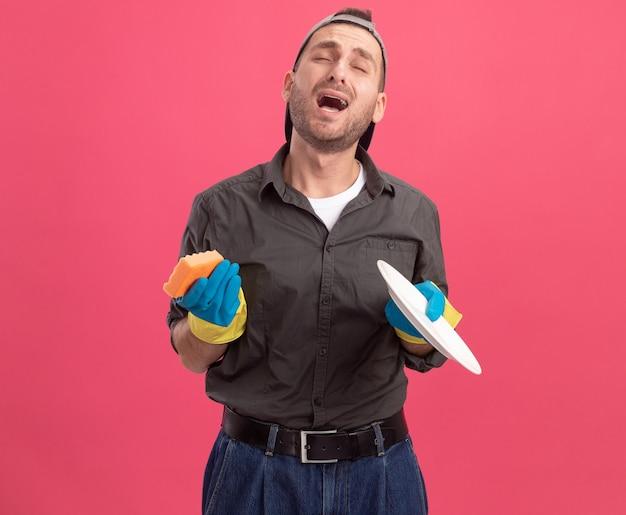 Jeune homme de ménage portant des vêtements décontractés et une casquette dans des gants en caoutchouc tenant une plaque et une éponge hurlant avec une expression agacée debout sur un mur rose