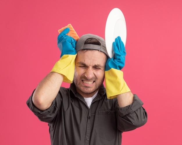 Jeune homme de ménage portant des vêtements décontractés et une casquette de gants en caoutchouc tenant la plaque et l'éponge fermant les oreilles avec une expression agacée debout sur un mur rose