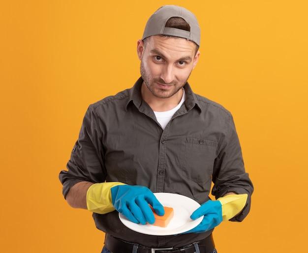 Jeune homme de ménage portant des vêtements décontractés et une casquette de gants en caoutchouc tenant la plaque et l'éponge à laver à sourire confiant debout sur le mur orange