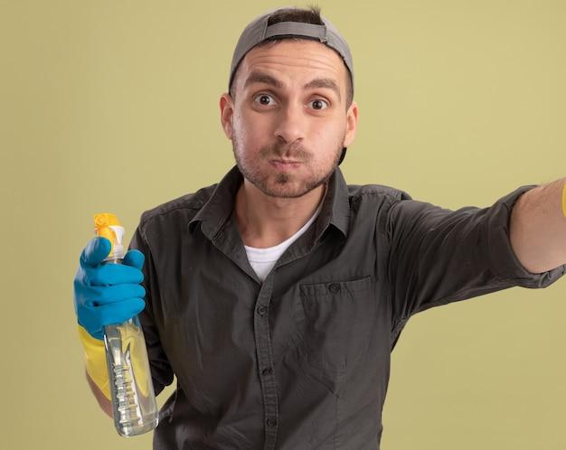 Jeune homme de ménage portant des vêtements décontractés et une casquette de gants en caoutchouc tenant un vaporisateur loking soufflant les joues debout sur le mur vert