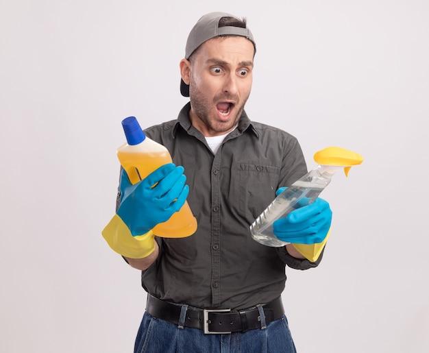 Jeune homme de ménage portant des vêtements décontractés et une casquette de gants en caoutchouc tenant un vaporisateur et des produits de nettoyage étonné et surpris debout sur un mur blanc