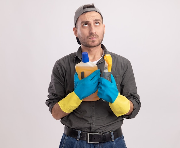 Jeune homme de ménage portant des vêtements décontractés et une casquette de gants en caoutchouc tenant un vaporisateur et des produits de nettoyage à la perplexité debout sur un mur blanc