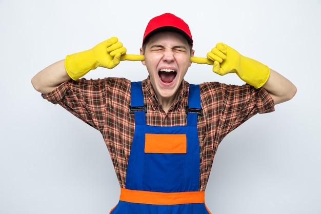 Jeune homme de ménage en uniforme et casquette isolé sur mur blanc