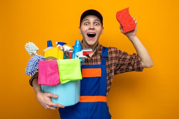 Jeune homme de ménage en uniforme et casquette tenant un seau d'outils de nettoyage avec une éponge isolée sur un mur orange