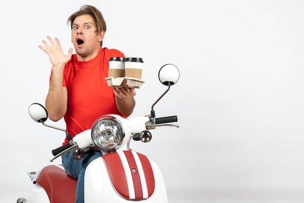 Jeune homme de messagerie choqué en uniforme rouge assis sur un scooter tenant des commandes sur le mur jaune