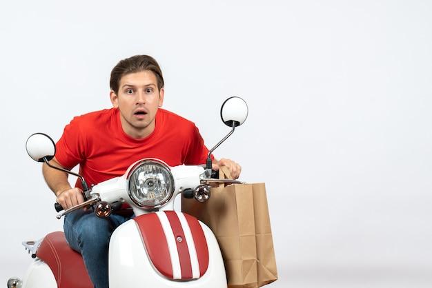 Jeune homme de messagerie concentré concentré en uniforme rouge assis sur un scooter tenant des commandes sur le mur jaune