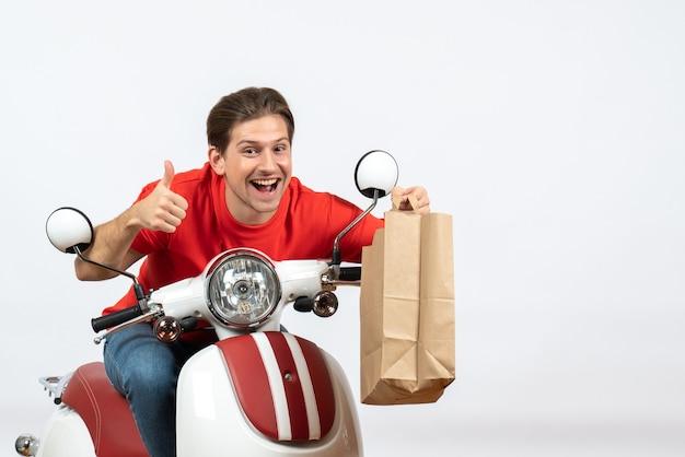 Jeune homme de messagerie heureux en uniforme rouge assis sur un scooter tenant des commandes et faisant un geste correct sur le mur jaune