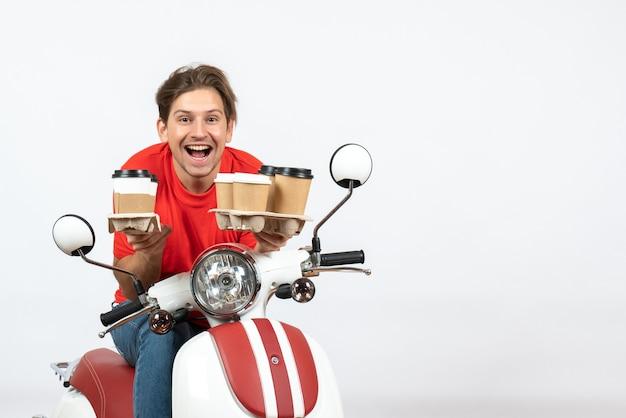 Jeune homme de messagerie heureux en uniforme rouge assis sur un scooter tenant des commandes sur le mur jaune