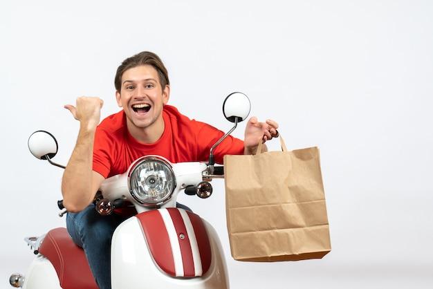 Jeune homme de messagerie heureux en uniforme rouge assis sur le scooter tenant les commandes et pointant vers l'arrière sur le mur jaune