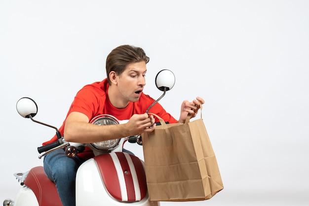 Jeune homme de messagerie occupé en uniforme rouge assis sur un scooter tenant un sac en papier sur un mur jaune