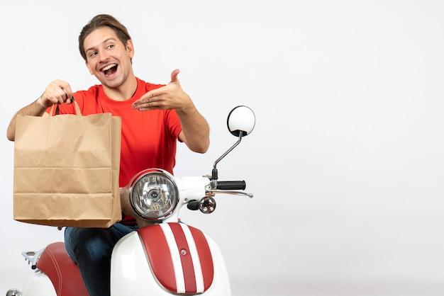 Jeune homme de messagerie souriant en uniforme rouge assis sur un sac de papier de pointage scooter sur mur blanc