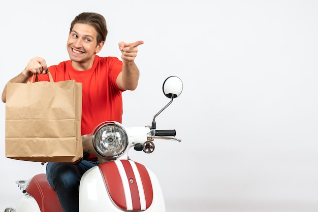 Jeune homme de messagerie souriant en uniforme rouge assis sur un scooter tenant un sac en papier pointant vers l'avant sur un mur blanc