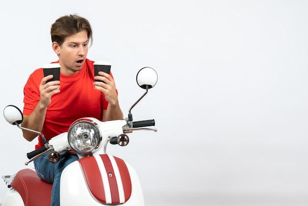 Jeune homme de messagerie surpris en uniforme rouge assis sur un scooter tenant des gobelets en papier sur un mur jaune