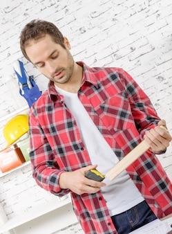 Jeune homme mesurant une planche de bois